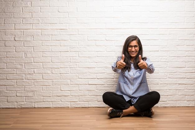 Mulher indiana nova senta-se contra uma parede de tijolo alegre e animado, sorrindo e levantando-a Foto Premium