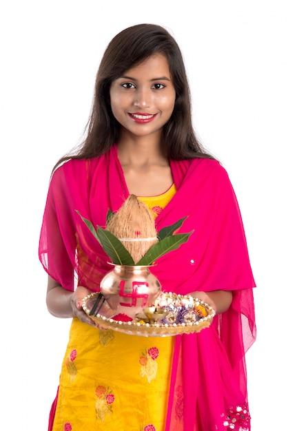 Mulher indiana segurando um kalash de cobre tradicional com pooja thali, festival indiano, kalash de cobre com folhas de coco e manga com decoração floral, essencial em pooja hindu. Foto Premium
