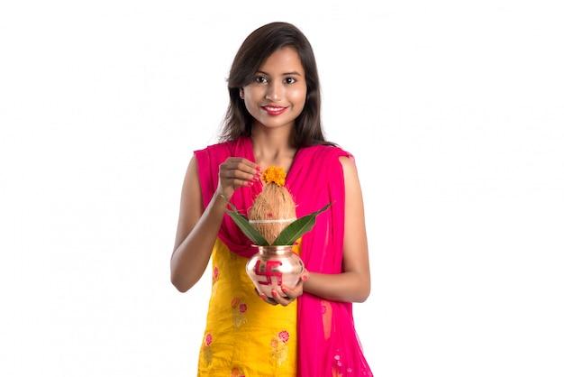 Mulher indiana segurando um kalash de cobre tradicional, festival indiano, kalash de cobre com coco e manga com decoração floral, essencial em hindu pooja. Foto Premium