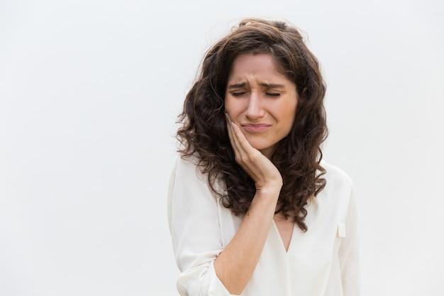 Mulher infeliz frustrada, sofrendo de dor de dente Foto gratuita