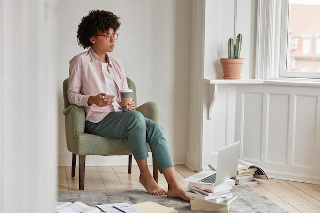 Mulher iniciante bem-sucedida e bem-sucedida gosta de bebida cappuccino, segura o copo para viagem, senta-se na poltrona, usa o telefone celular e o laptop Foto gratuita