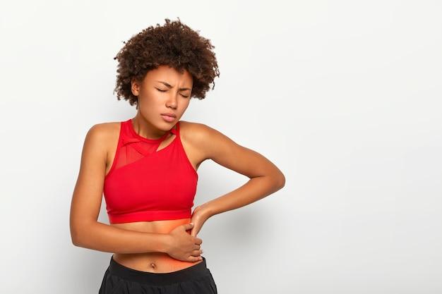 Mulher insatisfeita segura o quadril dolorido, tem inflamação nos rins, toca o local da dor perto das costelas marcado com um ponto vermelho, usa sutiã esportivo Foto gratuita