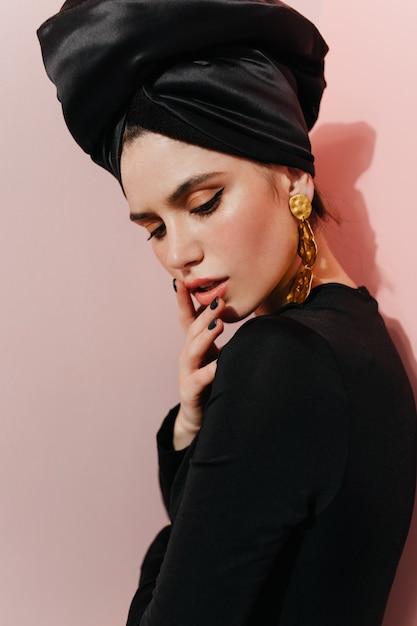 Mulher inspirada com turbante preto olhando para baixo Foto gratuita