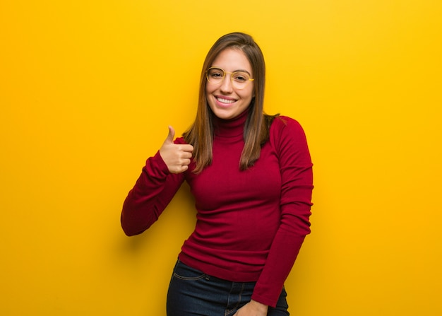Mulher intelectual nova que sorri e que levanta o polegar acima Foto Premium