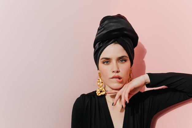 Mulher interessada em turbante em pé na parede de luz Foto gratuita