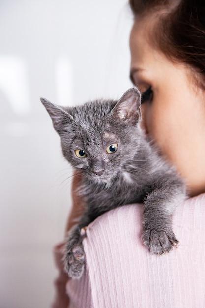 Mulher irreconhecível acariciando um gato de rua resgatado de um abrigo. estilo de vida com animais em casa. Foto Premium