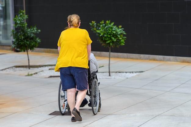 Mulher irreconhecível empurrando cadeira de rodas com uma pessoa com deficiência, vista traseira Foto Premium