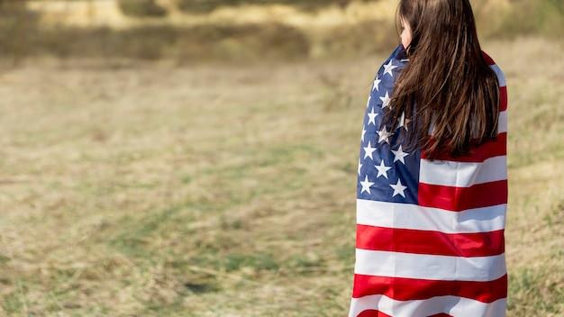 Mulher irreconhecível, envolvendo na bandeira do eua no dia da independência Foto gratuita