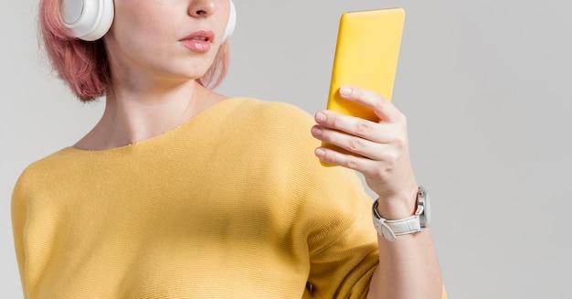 Mulher irreconhecível, olhando para o telefone Foto gratuita