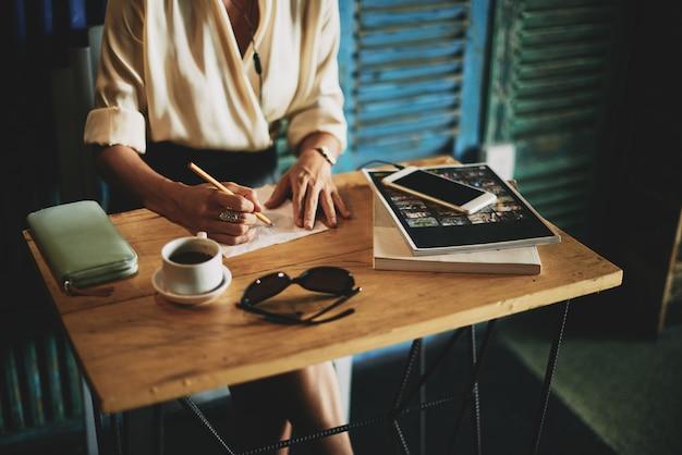 Mulher irreconhecível, sentado à mesa no café e escrevendo no guardanapo Foto gratuita