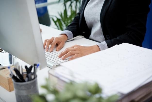 Mulher irreconhecível, sentado na mesa no escritório e digitando no teclado Foto gratuita