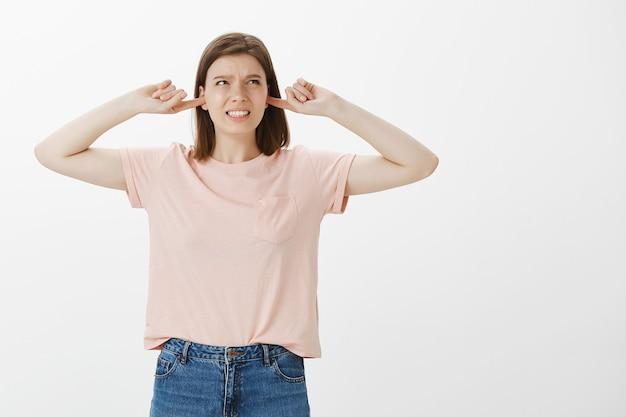 Mulher irritada fazendo careta devido ao barulho alto, ouvidos fechados e reclamando de um som irritante Foto gratuita