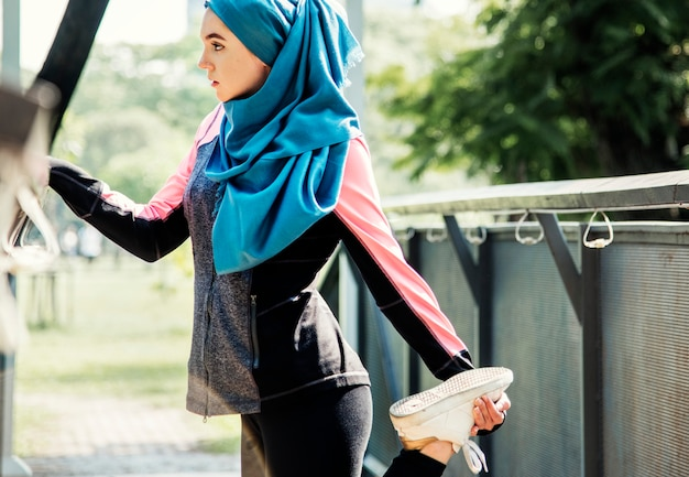 Mulher islâmica alongamento após treino no parque Foto Premium