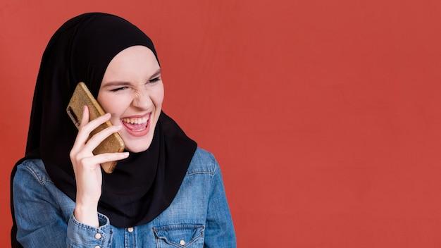 Mulher islâmica em hijab chamando por telefone Foto gratuita