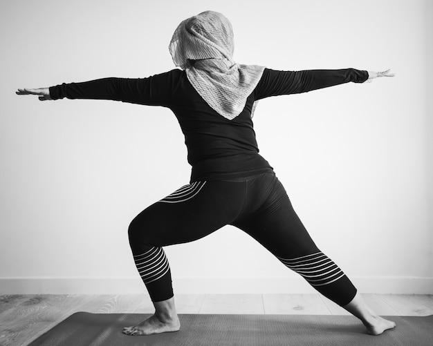 Mulher islâmica fazendo yoga no quarto Foto gratuita