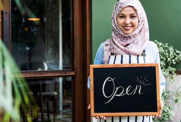 Mulher islâmica, pequeno, proprietário negócio, segurando, quadro-negro, com, sorrindo Foto gratuita