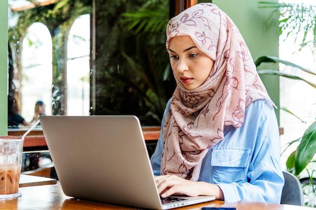Mulher islâmica sentado e usando laptop Foto Premium