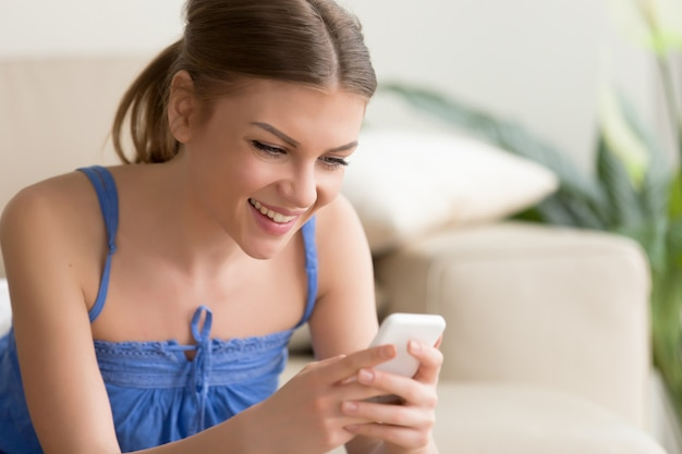 Mulher jogando jogos para celular no celular em casa Foto gratuita