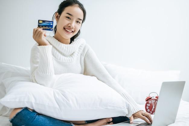 Mulher jogando laptop e segure um cartão de crédito. Foto gratuita