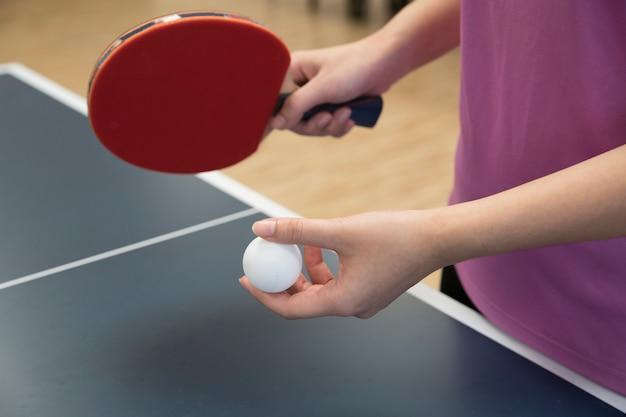 Mulher, jogando tênis tabela, com, a, raquete, e, pingue pong, bola, em, posição servindo Foto Premium