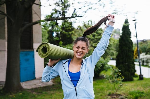 Mulher jovem alegre esportes caminhando no parque urbano, segurando o tapete de fitness. Foto gratuita