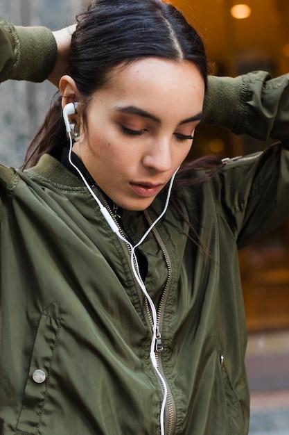 Mulher jovem, amarrando, dela, cabelo, escutar música, ligado, fone ouvido Foto gratuita
