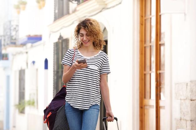 Mulher jovem, andar, com, sacolas, e, telefone móvel Foto Premium