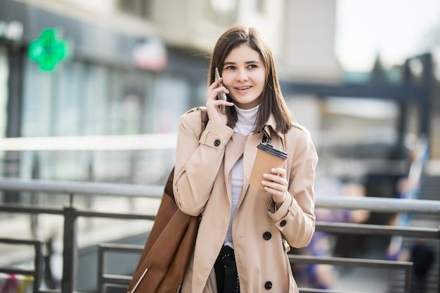 Mulher jovem, andar rua, segurando, xícara café, telefone Foto gratuita