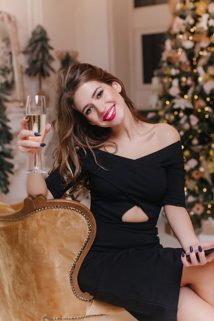 Mulher jovem animada com maquiagem na moda, levantando um copo de vinho com um sorriso. alegre garota europeia usa vestido preto para comemorar o natal em casa. Foto gratuita