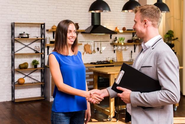 Mulher jovem, apertando mão, com, um, homem negócios Foto gratuita