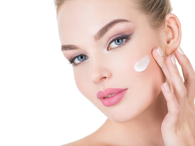 Mulher jovem aplica creme cosmético no rosto. Foto gratuita