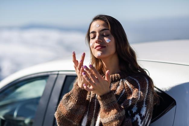 Mulher jovem, aplicando, protetor solar, ligado, dela, rosto, em, paisagem neve Foto Premium