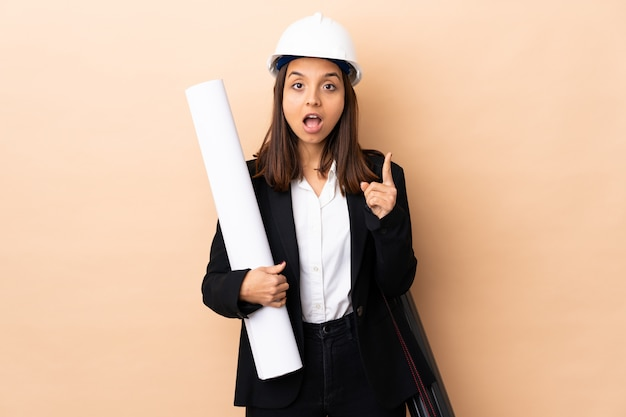 Mulher jovem arquiteto segurando plantas sobre fundo isolado, pensando uma idéia apontando o dedo para cima Foto Premium