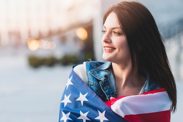Mulher jovem, arregaçando, em, bandeira americana Foto gratuita