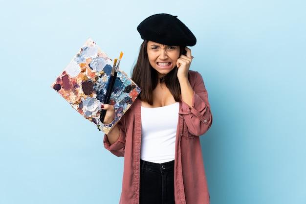 Mulher jovem artista segurando uma paleta nas orelhas frustradas e coning azuis isoladas Foto Premium