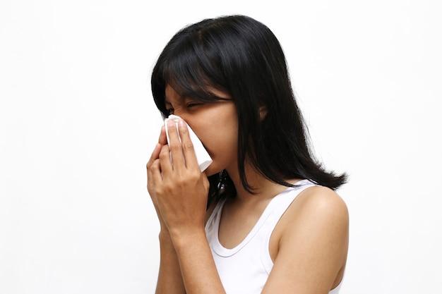 Mulher jovem asiática espirrando ou tossindo isolado no branco Foto Premium