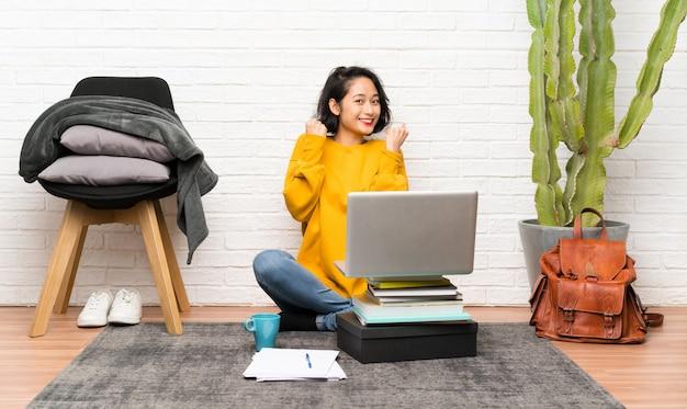 Mulher jovem asiática sentada no chão comemorando uma vitória Foto Premium