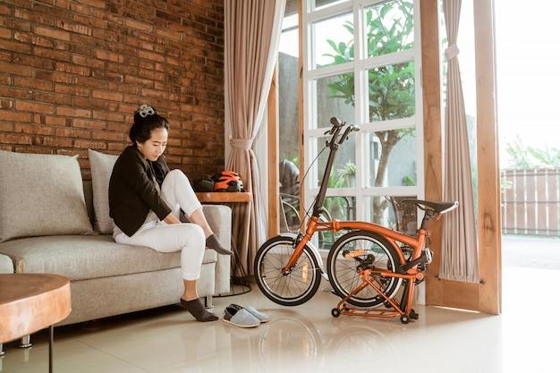 Mulher jovem asiática sentada no sofá usando meias quando se preparar para ir ao trabalho Foto Premium