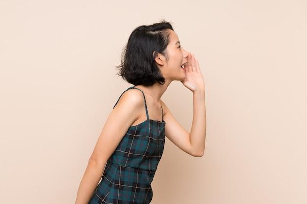 Mulher jovem asiática sobre parede amarela isolada gritando com a boca aberta para a lateral Foto Premium