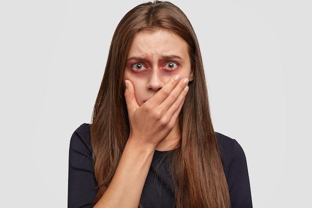 Mulher jovem assustada com hematomas posando contra a parede branca Foto gratuita