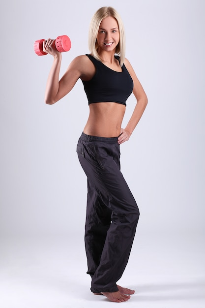 Mulher jovem atleta com halteres Foto gratuita