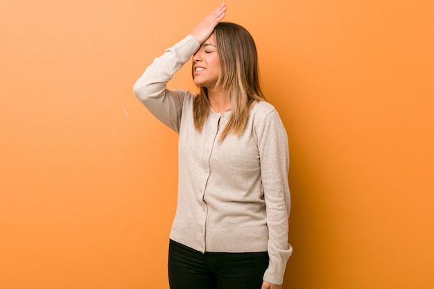 Mulher jovem autêntica carismática pessoas reais contra uma parede esquecendo algo, batendo na testa com a palma da mão e fechando os olhos. Foto Premium