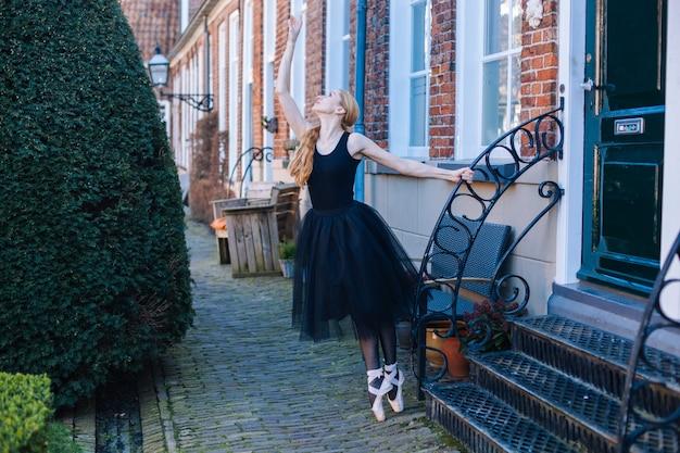 Mulher jovem bailarina com cabelo vermelho em traje de balé e sapatilhas está em bela pose dançando na rua. Foto Premium