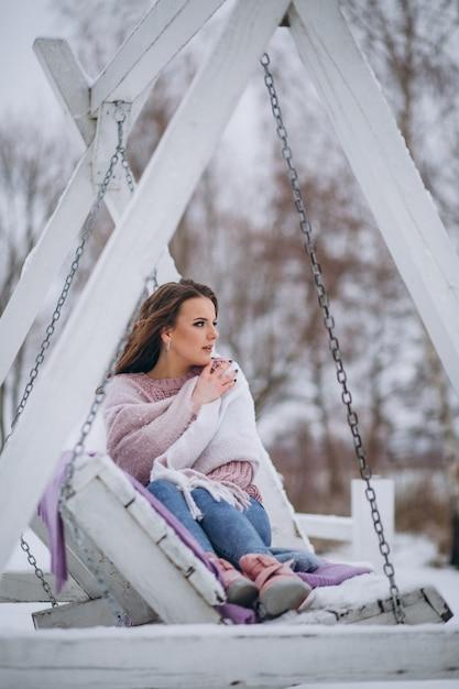 Mulher jovem, balançando, em, um, parque inverno Foto gratuita