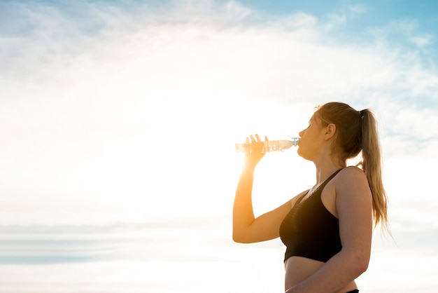 Mulher jovem, bebendo, água, de, um, garrafa Foto gratuita