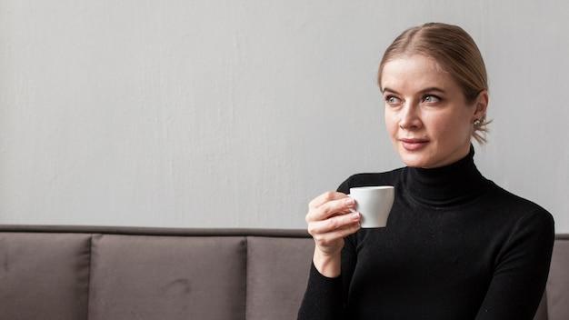 Mulher jovem, bebendo café Foto gratuita
