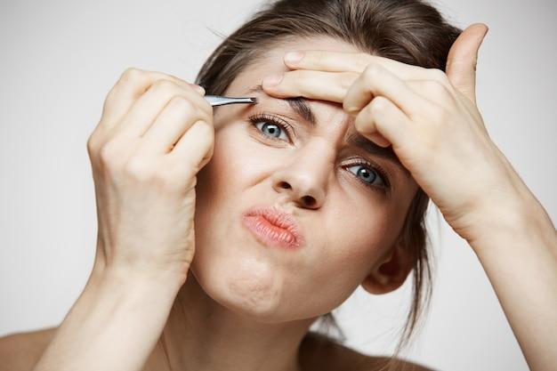 Mulher jovem bonita com sobrancelhas de tweeze pele limpa perfeita, fazendo careta. beleza e spa. Foto gratuita
