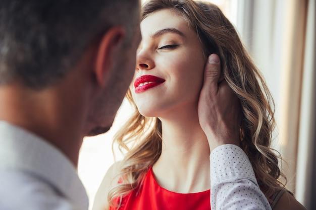 Mulher jovem bonita, desfrutando de seu homem tocando Foto gratuita