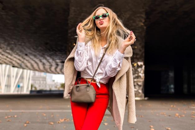 Mulher jovem bonita hippie posando na rua perto de centros de negócios modernos, vestindo roupa de escritório da moda e casaco de caxemira, enviando um beijo e aproveitou o dia fresco de outono, cores enfraquecidas. Foto gratuita