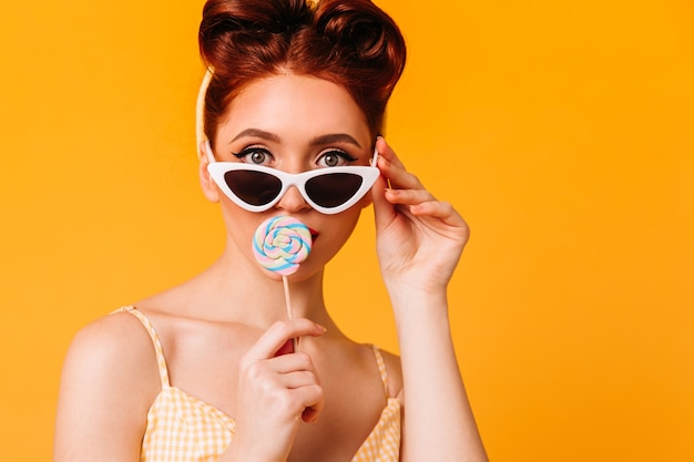 Mulher jovem bonita lambendo rebuçados. vista frontal da garota pin-up gengibre em óculos de sol. Foto gratuita